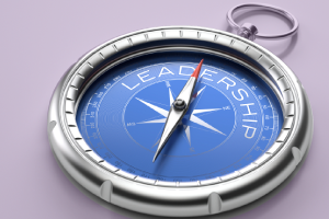 Photo of compass with arrow pointing toward word leadership.